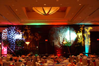 A banquet room with many tables and decorative floral lighing.