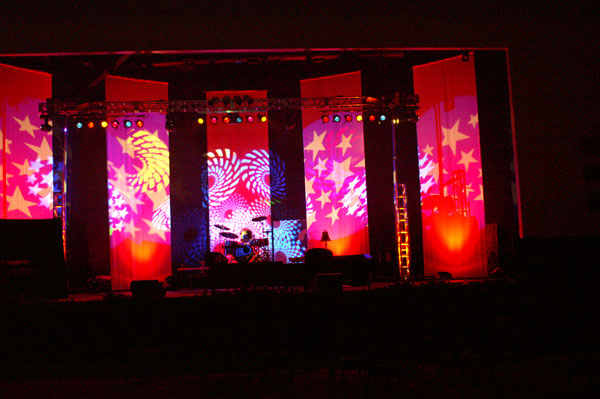 A stage set up for a concert with multi-colored stars and swirls